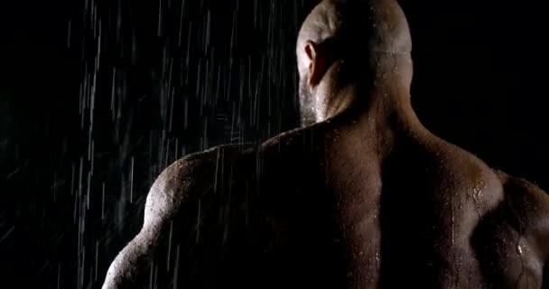 Egy nagyon nagy sportos, izmos, kopasz férfi áll az esőben. Vízcseppek csöpögnek le a széles hátán. sötét kulcs