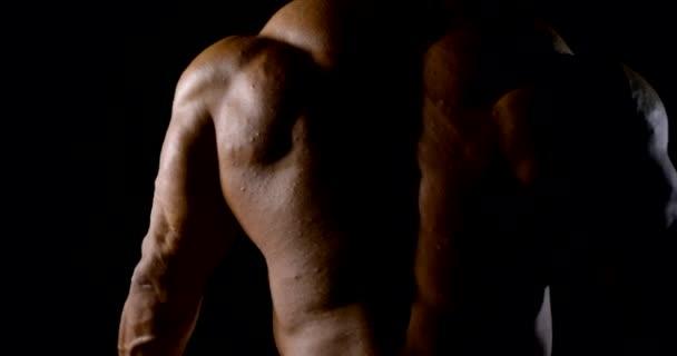 Nahaufnahme des verspannten muskulösen Rückens eines kahlköpfigen Bodybuilders. dunkler Schlüssel