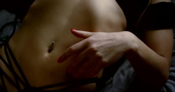 Detailní záběr na krásné tělo tmavovlasé ženy v sexy černém spodním prádle, leží na posteli, přejíždí si rukou po břiše a žebrech, má propíchnutý pupík.