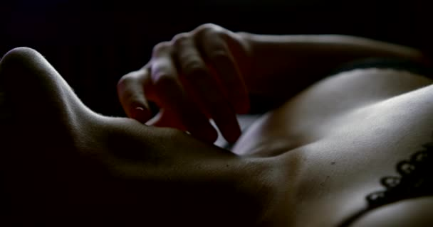 Nahaufnahme der schönen Brüste und des Halses einer Frau in sexy schwarzen Dessous, sie liegt auf dem Bett, sie läuft mit der Hand über sich selbst