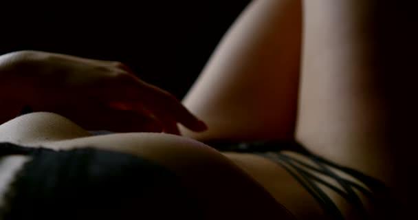 Nahaufnahme eines schönen Bauches und der Rippen einer Frau in sexy schwarzen Dessous, sie liegt auf dem Bett, sie läuft mit der Hand über ihren Bauch.