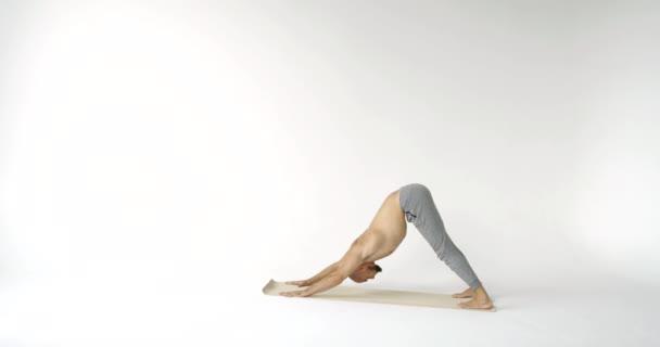 muž mění jóga asany na podložce, natahuje hlavu nahoru a dolů, napíná svaly na těle