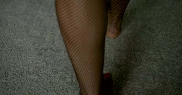 woman dressed in fishnet stockings is stepping in room over grey carpet, closeup of feet