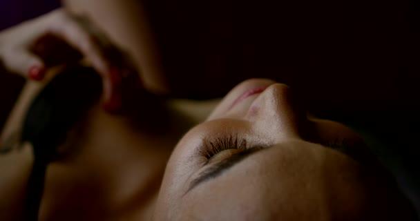 sinnliche Frau in schwarzen sexy Dessous streichelt ihre Brust liegend im Schlafzimmer
