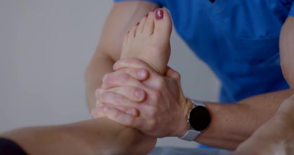 foot massage by chiropractor in modern osteopathic clinic, masseur is massaging female feet