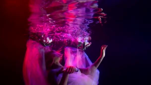 sexy žena se drží nad vodou v akváriu a postupuje nahoru, romantické pohádky koncept