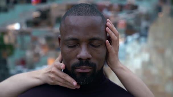 zblízka portrét Afroameričana opřeného o zrcadlovou stěnu, ruce evropské ženy jemně dotýkají tváře muže.