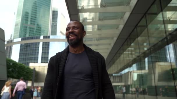 afro-american man is walking at city, laughing and putting sunglasses at face