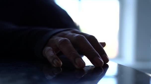 Etnická ruka poklepává prsty na stůl. Afroameričan.