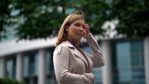 Üzletasszony sétál az irodaépület előtt. Egy női vállalkozó lassított felvételben körülnéz.
