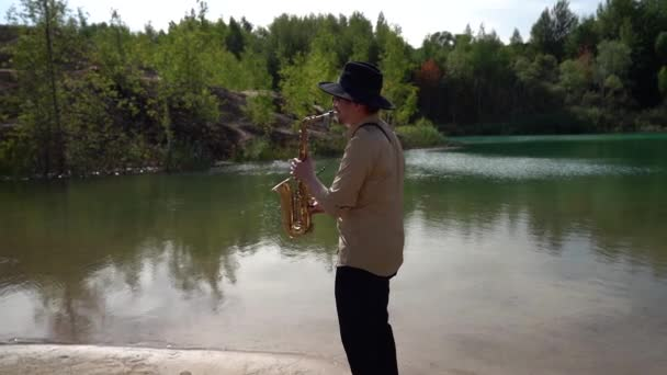male saxophonist is playing music at nature, calm landscape with lake and forest
