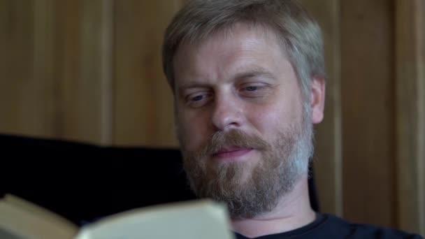 Portrét muže středního věku, jak čte doma knihu. Ten vousáč vypadá zasněně..