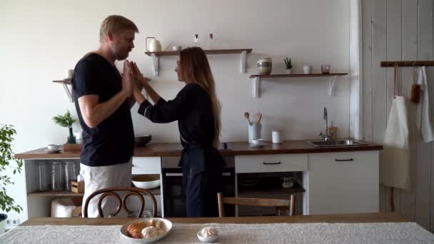 Morning at the kitchen table, quick Breakfast - croissants, marshmallows. Bearded husband and young wife dancing in the kitchen, smiling.