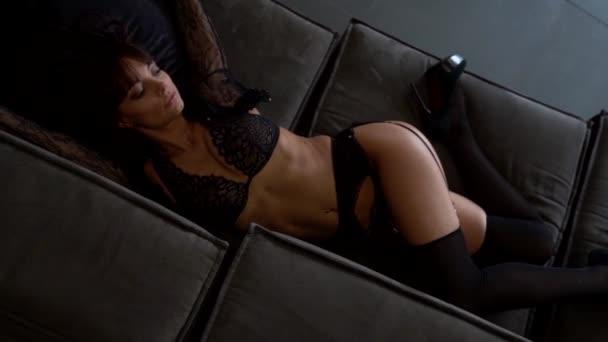 Egy csábító nő Lacy fehérneműben fekszik az ágyban. Erotikus nő álmodik szex egy sötét belső