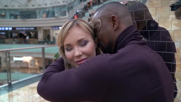 Afričan objímá blondýnu u zdi v nákupním centru. žena zavřela oči
