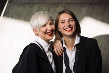 portrait of  two laughing women in classic suits posing against geometrical concrete wall outdoors