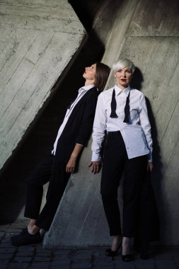 full length shot of two women in classic suits posing against geometrical concrete wall outdoors