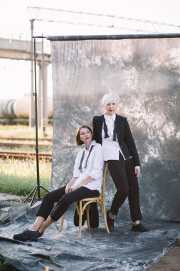 full length shot of two women in classic suits posing against studio background outdoors