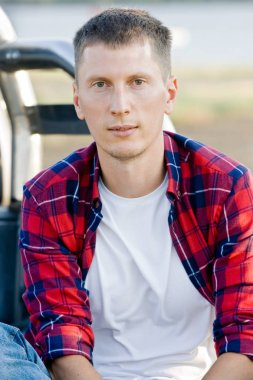 Portrait of young man in red checkered shirt sit in the car
