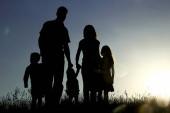 Siluetta di una famiglia felice con i bambini sul tramonto
