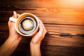 ženské ruce držící šálek kávy na dřevěné pozadí