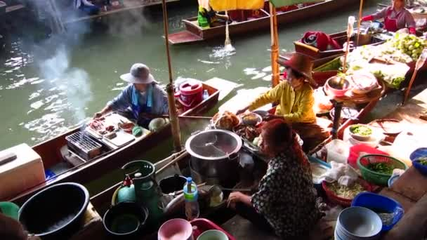 Street vendor in boat at traditional floating market in Thailand