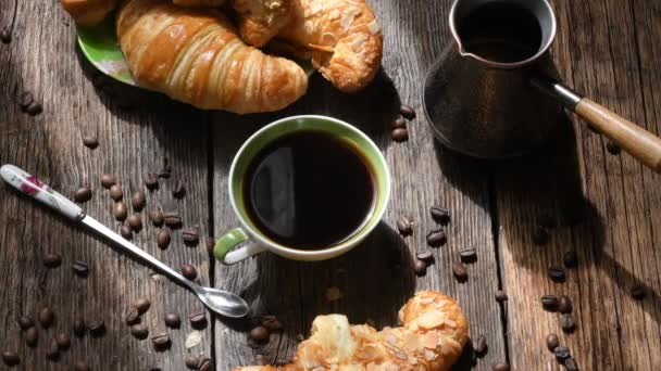 Coffee composition. Coffee Cup, croissants, coffee beans and copper coffee maker on old wooden table background. 4 K picture