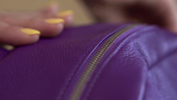Closeup ženy ruce, otevření zip Dámské kabelky. Žluté nehty, fialová taška