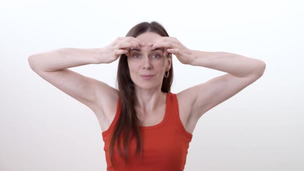 Portrait of brunette woman doing horizontal movement of fingers over the eyebrows to reduce wrinkles between the eyebrows. Isolated on the white background.