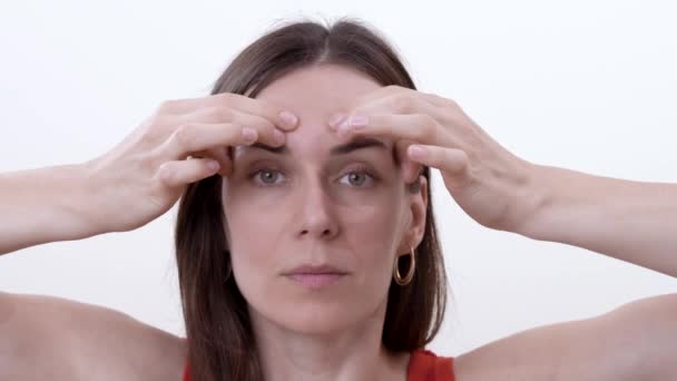 Close up of brunette woman doing horizontal movement of fingers over the eyebrows to reduce wrinkles between the eyebrows. Isolated on the white background.
