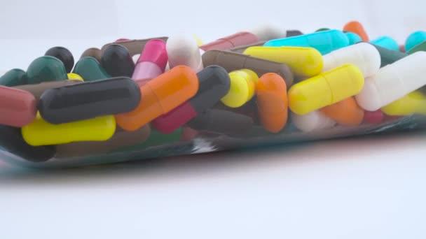 Viele der bunten Hartstärkekapseln rotieren in einer transparenten Glasflasche auf dem Plattenteller. isoliert auf weißem Hintergrund. Nahaufnahme Makro.