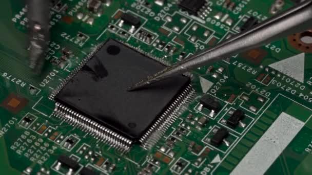 Desolder a felületre szerelt elektronikus chip mikroprocesszor a forrasztópáka a az áramköri lap segítségével. Áttördelés kapcsolatok a mikroprocesszor. Vértes makró.