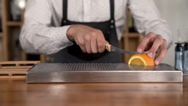 Hands of a bartender cutting orange fruit on the bar counter. Closeup macro.