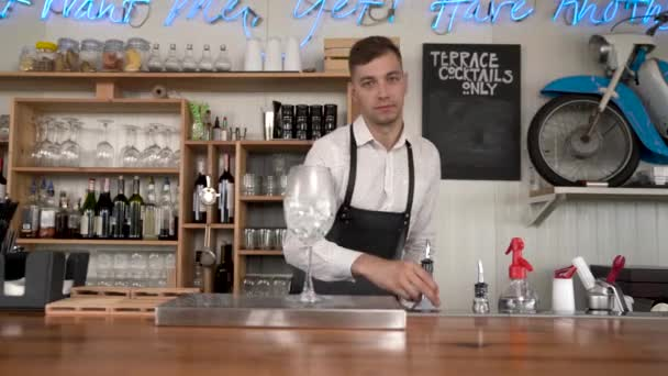 A handsome young bartender pours a water to the glass with ice cubes. Bar counter.