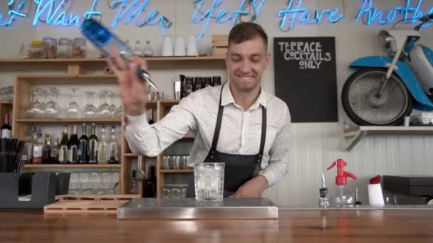 A handsome young bartender pours a blue curacao liquor into a glass with ice cubes at the bar counter.