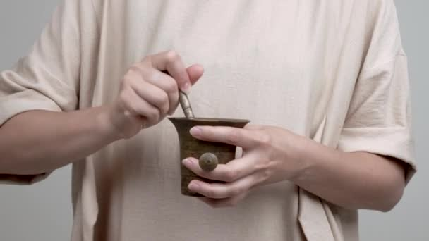 Womans hands are holding a mortar and pestle. She adds rose petals and starts mortaring them gently, moving anticlockwise.