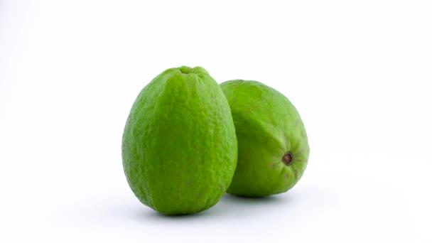 Dvě celé jablko guava ovoce se otáčejí na gramofonu izolovaných na bílém pozadí. Zblízka. Makro