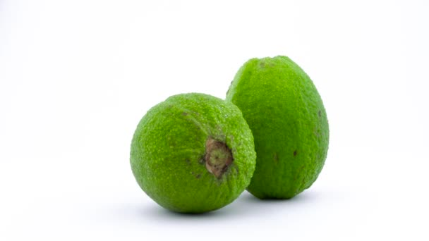 Dvě celé jablko guava ovoce s vodou kapky. Otočení na točnu izolovaných na bílém pozadí. Zblízka. Makro