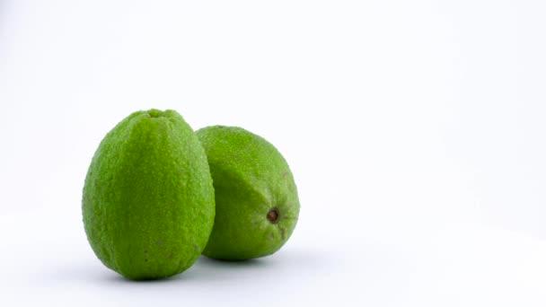 Poloviční rám ze dvou apple guava ovoce s vodou kapky. Otočení na točnu izolovaných na bílém pozadí. Zblízka. Makro