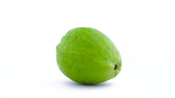 Jeden celý apple guava ovoce se otáčí na gramofonu izolovaných na bílém pozadí. Zblízka. Makro