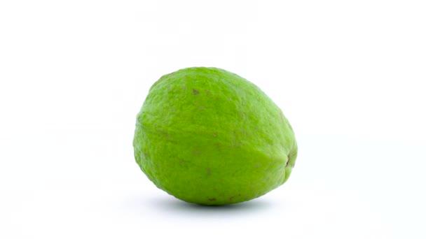 Jeden celý apple guava ovoce se otáčí na gramofonu. Kapky vody na kůži se objeví během rotace. Izolované na bílém pozadí. Detail. Makro