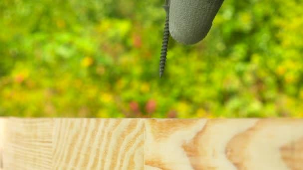 Detailní záběr na elektrický pohon šroubovák kroucení černá Samořezný šroub šroub v dřevěné prkno. Venku. Kopírovat prostor.