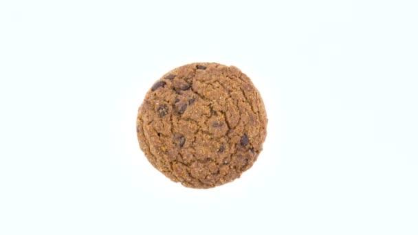 Pohled shora z výšky jednoho měkké a žvýkací čokoláda čip ovesné vločky cookies otočení na gramofonu. Izolované na bílou barvu pozadí. Detail. Makro.