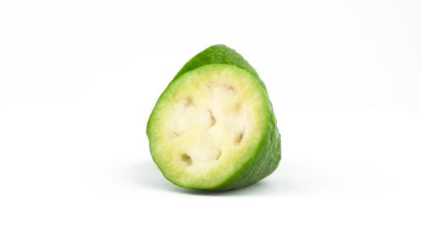 Dvě poloviny feijoa zralé ovoce s vodou kapky. Otočení na točnu izolovaných na bílém pozadí. Zblízka. Makro
