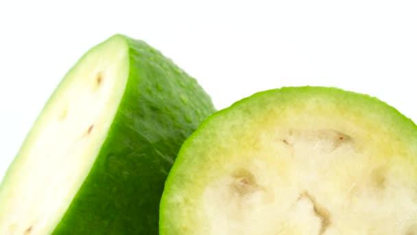Makro střelbu z horní části ze dvou polovin feijoa ovoce. Pomalu se otáčející na gramofonu izolovaných na bílém pozadí. Detail