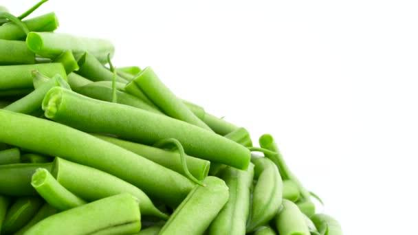 Makroschießen von frisch geschnittenen grünen Bohnen stapeln sich. Halbrahmen. sich langsam auf der Drehscheibe drehend. isoliert auf weißem Hintergrund. Nahaufnahme.