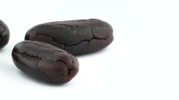 vertikale Hälfte aus vier gerösteten Kakaobohnen. Langsam rotierend auf der Drehscheibe, isoliert auf weißem Hintergrund. Nahaufnahme. Makro. Kopierraum.