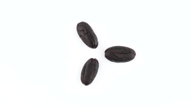 Blick von oben auf drei geröstete Kakaobohnen. Drehen auf der Drehscheibe isoliert auf weißem Hintergrund. Nahaufnahme. Makro.