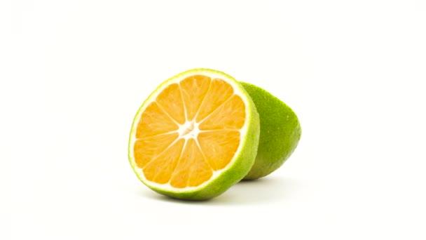 Dvě poloviny zelená mandarinka ovoce s vodou kapky. Otáčení na gramofonu. Izolované na bílém pozadí. Detail. Makro.