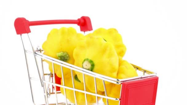 Closeup supermarket vozíku s žlutým pattypan tykve. Nákupní košík se pohybuje v rámu. Izolované na bílém pozadí